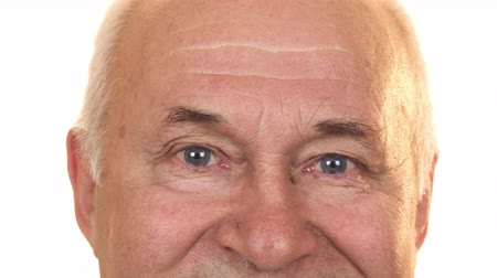 positive ageing : Close up of the blue eyes of a cheerful senior man isolated