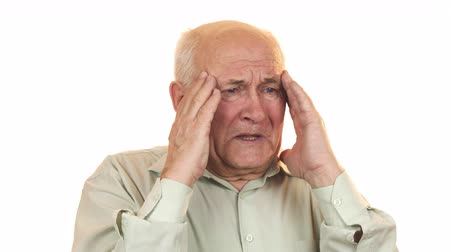 gripe : Senior man having a headache rubbing his temples