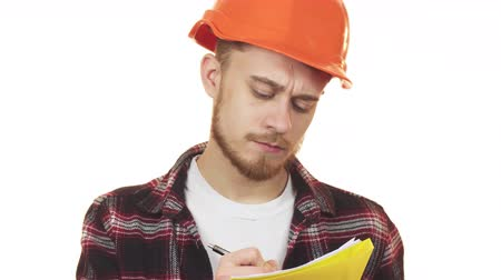 professionalism : Young professional male architect in a hardhat making notes Stock Footage