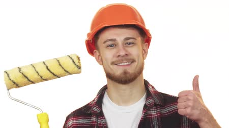megbízható : Happy young male builder holding paint roller showing thumbs up