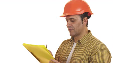 professionalism : Mature foreman builder in a hardhat making notes on clipboard