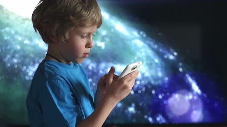 gry komputerowe : Boy playing with smartphone. Close up of boy and mobile device in hands sitting on the background of cosmic sky Wideo