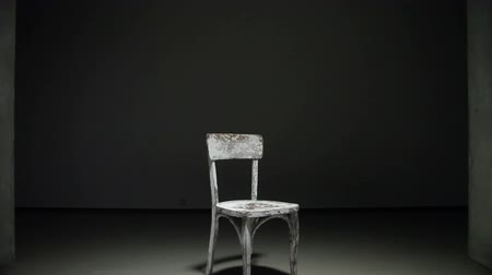 stylization : white old wooden chair are in lit black room steadicam shot