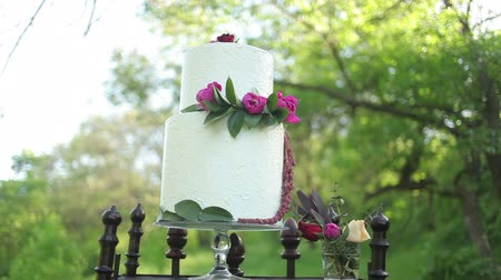 tiered : On the antique wooden stand beautiful wedding cake with flowers on it in the sunlight. Steadicam shot