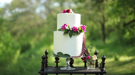 wedding cake : On the antique wooden stand beautiful wedding cake with flowers on it in the sunlight. Steadicam shot