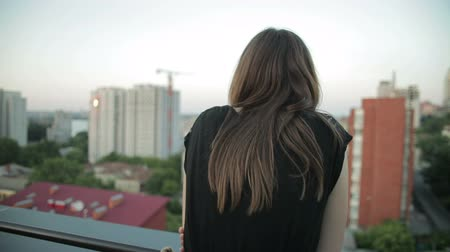 melankoli : Young pensive woman standing on a balcony and looking at cityscape Stok Video