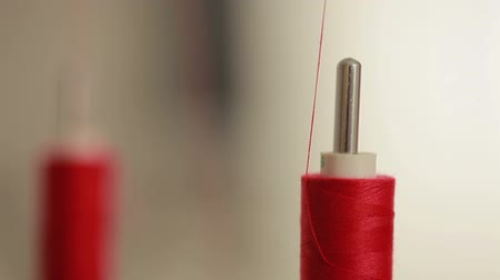 lem : Sewing bobbin being wound up on a sewing machine with red thread. Machine in clothing industry production. Close up.