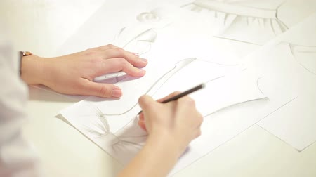 munkaruha : Female fashion designer drawing sketches for clothes in atelier.