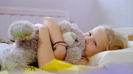 waking : Pretty little blonde girl wakes up in her bed and smiles at the camera early in the morning. Girl hugs a teddy bear.