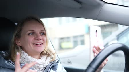 follower : Young woman blogger in winter clothes sitting in car and talking with followers, live streaming, looking to smartphone screen. Social media, video chat and technology concept.