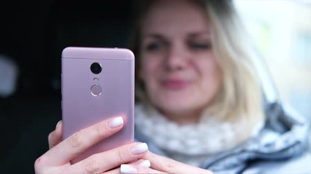 follower : Blurred blonde woman blogger in winter clothes sitting in car and talking with followers, live streaming, looking to smartphone screen. focus on phone