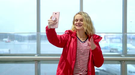 follower : Young woman blogger in red winter clothes in airport talking with followers, live streaming, looking to smartphone screen. Traveling, Social media, video chat and technology concept.