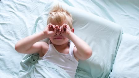 acordar : A little blond boy lies in bed and smiles, the boy rubs his eyes with his hands in the early morning. Time to wake up. Stock Footage