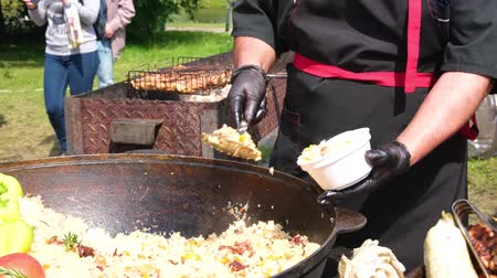 wok food : A cook in black clothes and gloves puts fragrant pilaf in a plate on street food from a huge cauldron. Street festive freshly prepared food. Meat and rice. A traditional dish of Asian cuisine