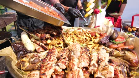 fornada : Street Food Festival. A chef in black clothes and gloves adds a new batch of sausages. Potatoes, grilled sausages, meat with sticks, barbecue. Food close up. Stock Footage