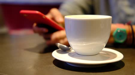латте : Coffee. Cropped woman picks up red phone, checks messages while drinking coffee in restaurant, cafe. Closeup woman hands with white cup. Dark warm toned scene Стоковые видеозаписи