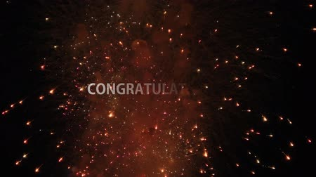 promoce : Appearing white text Congratulations on the background of the Colored firework lights exploding closeup. Dazzling fireworks on black night sky. Festive, winner and celebration concept Dostupné videozáznamy