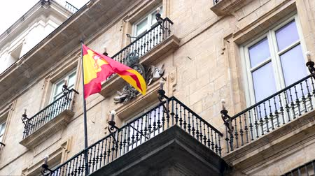 záhyby : Spanish flag waving by the wind at the entrance of top of governmental building in Madrid.
