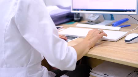 cardiologista : Woman doctor surgeon in white uniform types on the computer keyboard the diagnosis and examination results. Hands close up. Modern medical technologies. Healthcare and medicine. 4k footage.