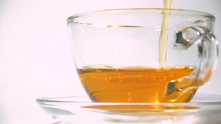 fabricado cerveja : Pouring aromating black tea from teapot into a matching transparent glass tea cup on white background closeup Vídeos