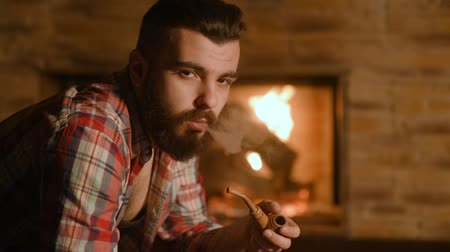 trubka : a young man with a beard hipster drinking tea in an iron circle and smokes a pipe in a wooden house on a background of fire.