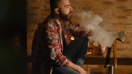 iron pipe : handsome man with a beard in a plaid shirt smokes an electronic cigarette and drinking tea on a background of fire in a wooden house. E-cigarette, wiper, wipe, lumberjack, loneliness Stock Footage