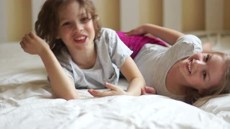 капелька : Cute kids cuddling and playing in bed.