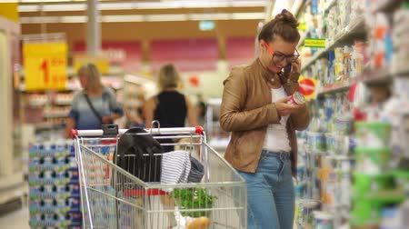 recados : Poland, Wroclaw. Woman Choosing Dairy Yoghurt in Supermarket. Young Mommy, Housewife, Milk Diet, Milk Proteins, Difficult Choice, Healthy Eating. The girl is talking on the mobile