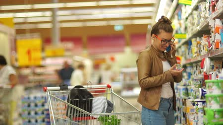 recados : Beautiful woman buys kefir in a supermarket. Young Mommy, Housewife, Milk Diet, Milk Proteins, Difficult Choice, Healthy Eating. The girl is talking on the mobile Stock Footage