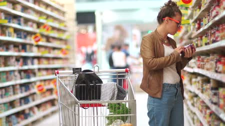 raflar : Portrait of a girl choosing tomato sauce or balsamic vinegar in a grocery store. The woman in the supermarket. Choice of products. Sunday shopping Stok Video