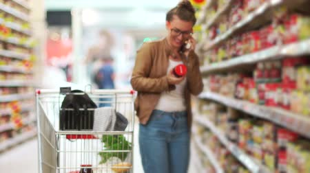 raflar : A young modern girl is shopping at a supermarket and talking on her cell phone. Sincere smile. The supermarket cart is full of products Stok Video