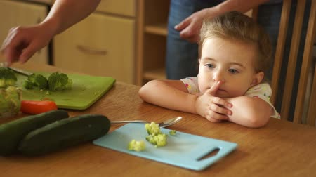 refusal to eat : Dad feeds her daughter. The little girl does not want to eat broccoli. She gets angry and turns away.