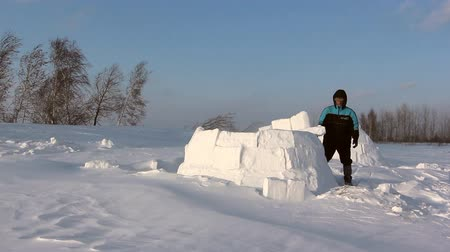 igloo : Man building an igloo in a blizzard in the winter