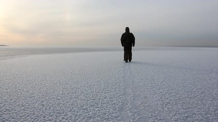 Man in warm clothes walking on a frozen river at sunset, Ob reservoir, Siberia, Russia