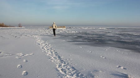 Man in a beige sweater running through the ice of a frozen river, Ob Reservoir, Russia
