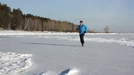 Man in a blue jacket running through the ice of a frozen river, Ob Reservoir, Russia