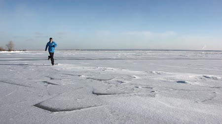 sideways : Man in a blue jacket running through the ice of a frozen river, Ob Reservoir, Russia