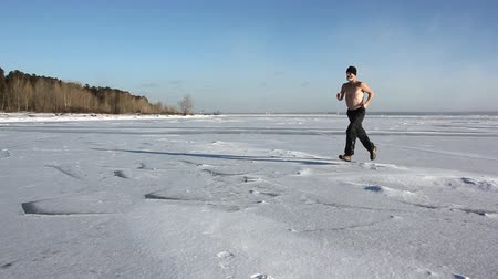 Man in a cap with a naked torso running through the ice of a frozen river, Ob Reservoir, Russia
