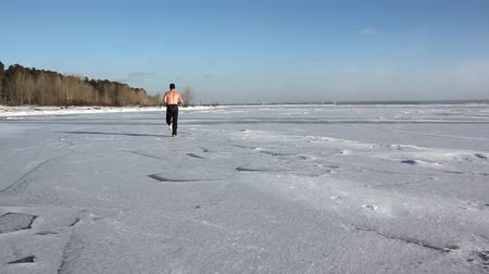 Barefooted man with a naked torso running through the ice of a frozen river, Ob Reservoir, Russia Dostupné videozáznamy