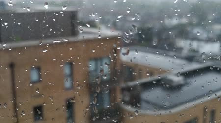 Rainy day in a city, water drops on window. Summer heavy rain and view from a top floor on a city. 4K.