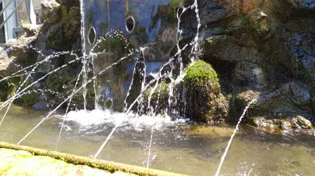 Artificial small waterfall with water shoots. Outdoor footage.