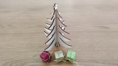 Tiny wooden tree with small Christmas gifts. Top view footage on wooden table. Wideo