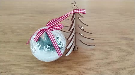 Christmas ball with fake snow top view footage. Footage from above on Christmas tree toy. Tiny wooden tree on the table. Wideo