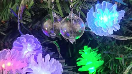 Stylish glass ball earrings hanging on Christmas tree. Unique pine tree cones flashing fairy lights. Close up footage of luxury present. Festive season decoration. Wideo