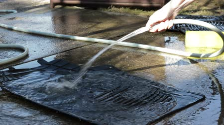 gąbka : Washing rubber floor mats for car. Womens hand holding a hose high pressure cleaner and washing rubber floor mats for car.