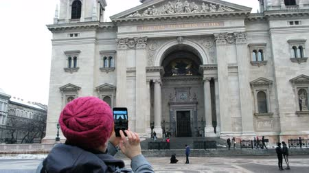 st stephen : BUDAPEST, HUNGARY - 18 JANUARY, 2019: Woman tourist making photo of St. Stephen Basilica by mobile. Budapest, Hungary Stock Footage