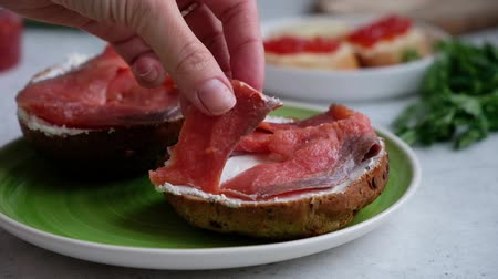 A chefs hand places slices of red salmon onto a sesame dark bread with cream cheese, slow motion