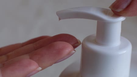 Finger push button on cream bottle in clean hand in bathroom. Skin care, hygiene and healthy life concept. Close up