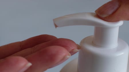 sanitize : Finger push button on cream bottle in clean hand in bathroom. Skin care, hygiene and healthy life concept. Close up