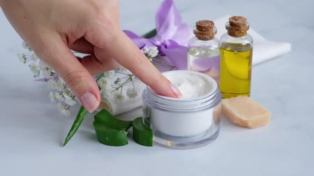 womans hand taking the cream with aloe vera from the jar with index finger Vídeos
